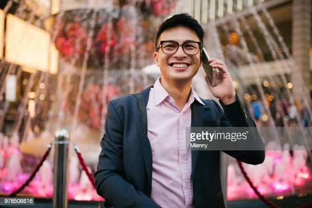 Chinese businessman on smart phone downtown Kuala Lumpur