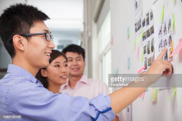 chinese businessman pointing to display in office - storyboard stock pictures, royalty-free photos & images