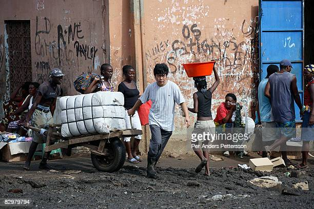 Chinese businessman pulls a cart with imported Chinese good with his Angolan workers on March 31 2007 at the Chinese market in Luanda Luanda is full...