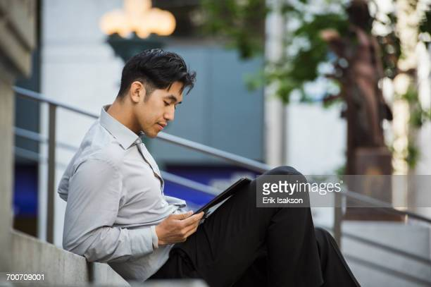 Chinese businessman reading digital tablet on staircase