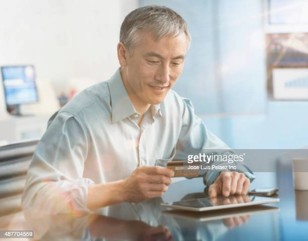 Chinese businessman shopping on digital tablet