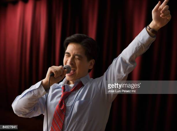 chinese businessman singing karaoke - one mature man only stock pictures, royalty-free photos & images