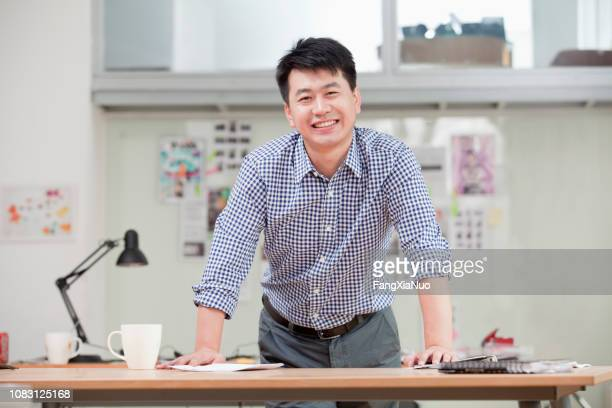 chinese businessman standing at desk - storyboard stock pictures, royalty-free photos & images