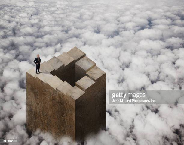 Chinese businessman standing on tower above clouds