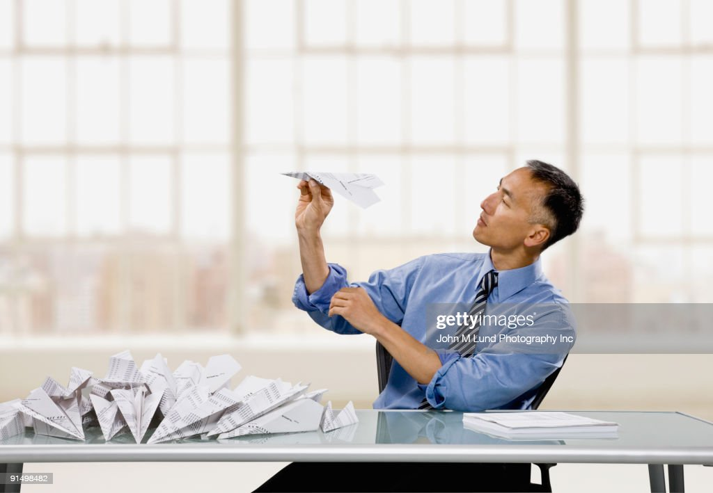 Chinese businessman throwing paper airplane : Stock Photo