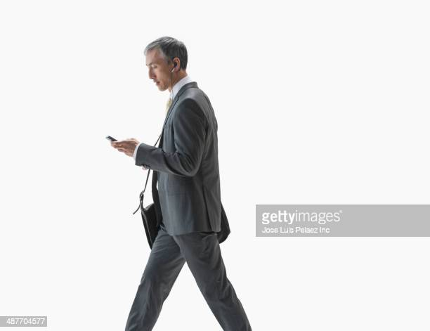 chinese businessman using cell phone - andando - fotografias e filmes do acervo