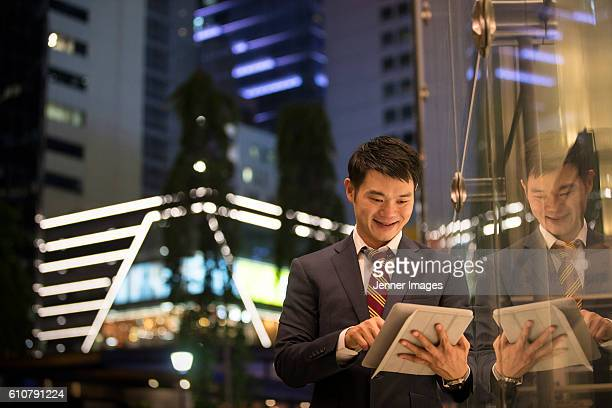 Chinese businessman using his Tablet device in Asian City at night.