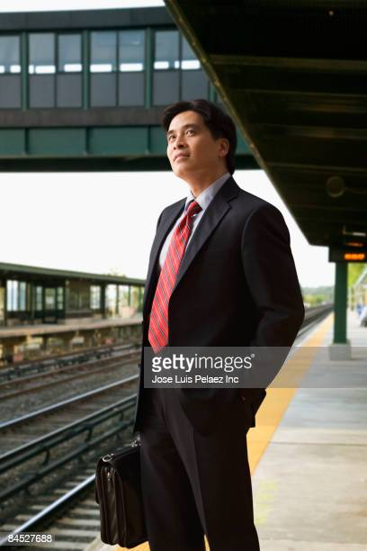 Chinese businessman waiting for train at depot
