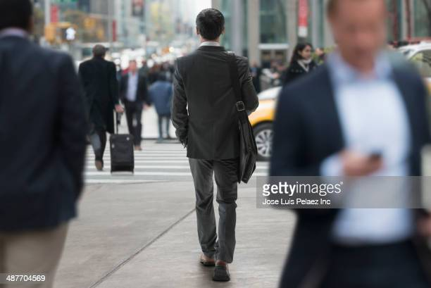 Chinese businessman walking on city street