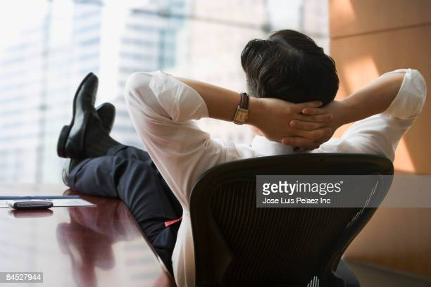 chinese businessman with feet up on desk - zurücklehnen stock-fotos und bilder