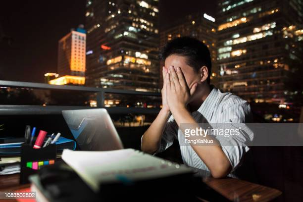 chinese businessman working at desk at night - overworked stock pictures, royalty-free photos & images