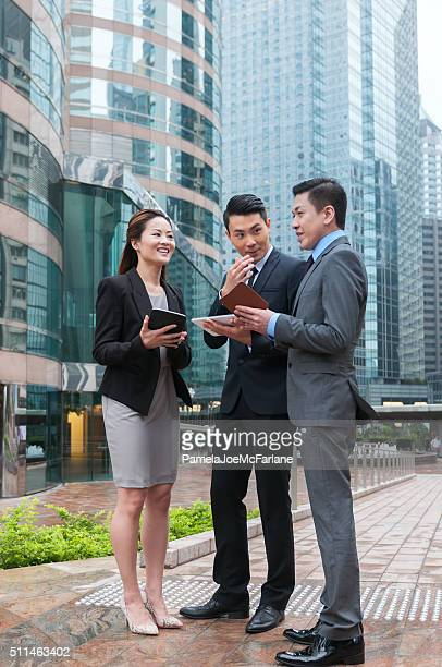 Chinese Businessmen and Businesswoman with Computer Tablets in Outdoor Meeting