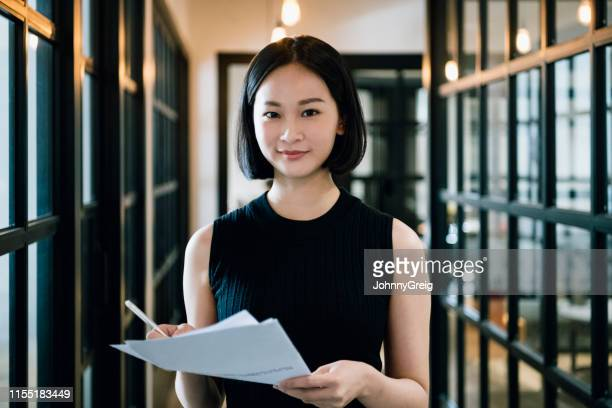 chinese businesswoman in her 30s holding paperwork and smiling - mid adult women stock pictures, royalty-free photos & images