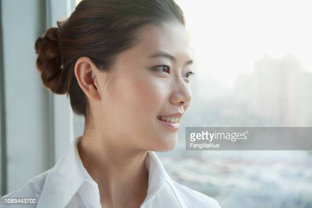 chinese businesswoman looking out window - day 1 stock pictures, royalty-free photos & images