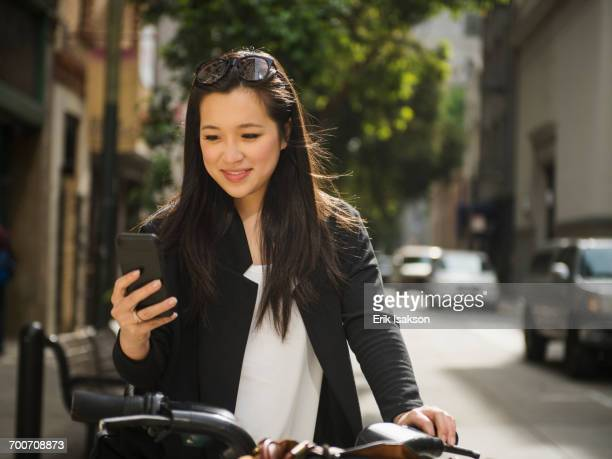 Chinese businesswoman on bicycle texting on cell phone