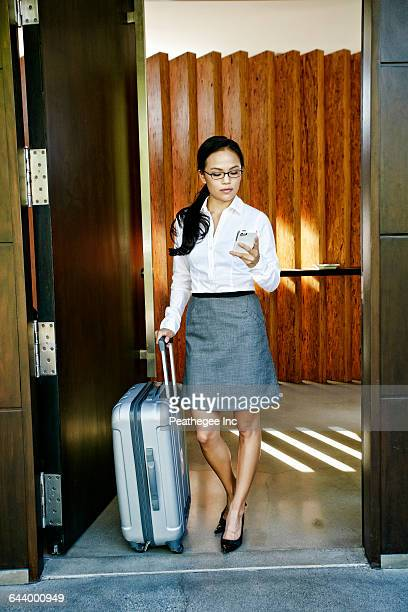 Chinese businesswoman rolling luggage in hotel doorway