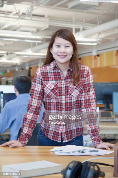 chinese businesswoman smiling at desk - minority groups stock pictures, royalty-free photos & images