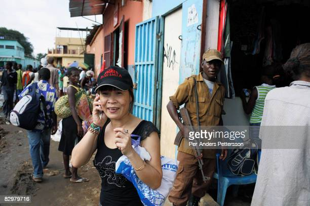Chinese businesswoman talks on her mobile phone outside a shop on March 31 2007 at the Chinese market in Luanda Luanda is full of newly arrived...