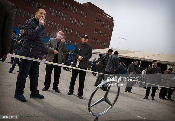 Chinese buyers look at a Mercedes sedan as they wait to bid at an auction of government vehicles on March 18 2015 in Beijing China The auction was...