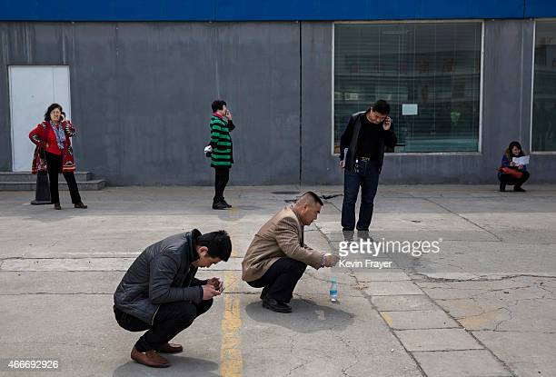Chinese buyers wait to bid at an auction of government vehicles on March 18 2015 in Beijing China The auction was held to selloff more than 100...