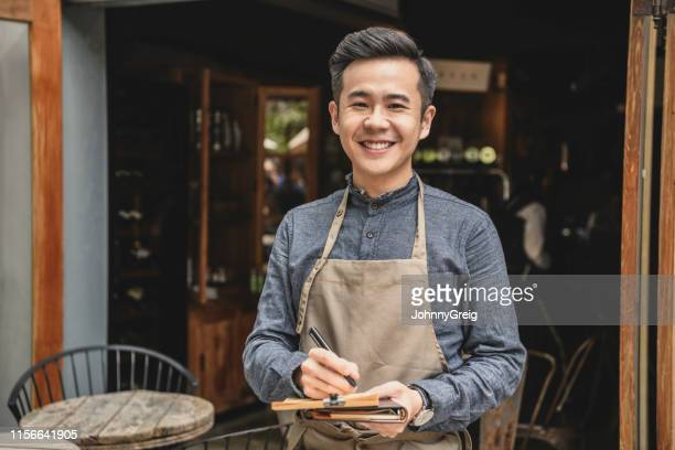 chinese cafe manager wearing apron by cafe - waiter stock pictures, royalty-free photos & images