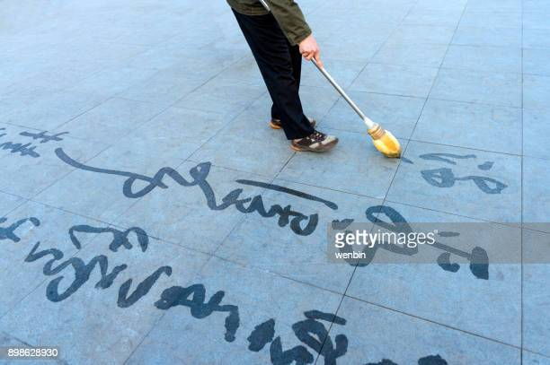 a chinese calligrapher is writing and writing on the square. - calligraphy stock photos and pictures