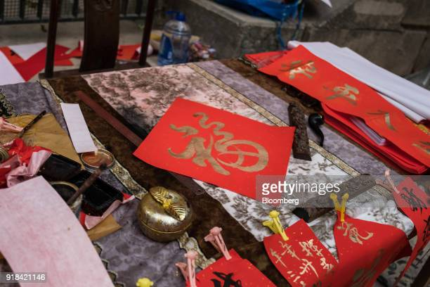 Chinese calligraphy decorations sit on sale at a market stall ahead of Lunar New Year in the Sheung Wan district of Hong Kong China on Wednesday Feb...