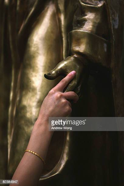 Chinese Catholic holds the hand of a statue of Saint Francis Xavier after mass at the government sanctioned Southern Church on August 17 2008 in...