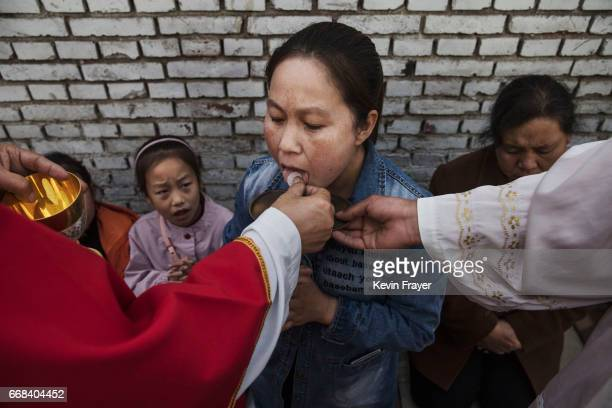 A Chinese Catholic woman takes communion at the Palm Sunday Mass during the Easter Holy Week at an underground or unofficial church on April 9 2017...