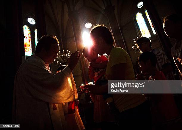 Chinese Catholic woman takes communion from a priest during a service for the Assumption of the Virgin Mary at a government sanctioned church on...