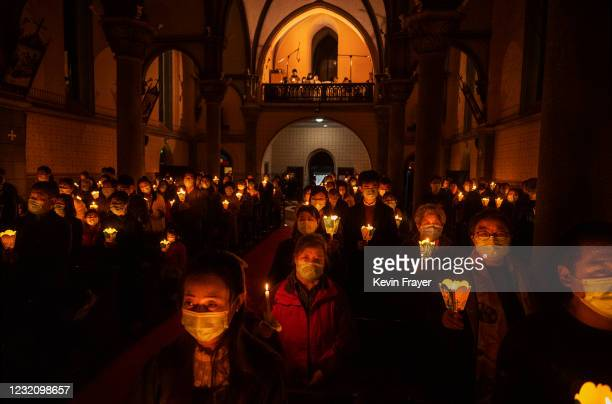 Chinese Catholic worshippers hold candles as part of the holy fire at an Easter mass at a Catholic church on April 3, 2021 in Beijing, China. With...
