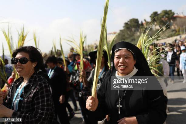 Chinese Catholic worshippers take part in the traditional Palm Sunday procession from the Mount of Olives to Jerusalem's Old City on April 14 2019...