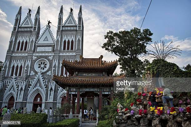Chinese Catholics arrange plastic flowers around a statue of the Virgin Mary at the government sanctioned Xishiku Catholic Church on August 14 2014...