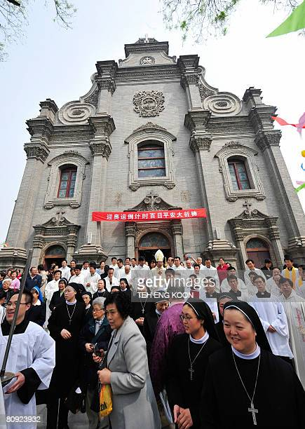 Chinese Catholics leave after a special prayer to mark 100 days until the start of the 2008 Beijing Olympic Games at a government approved Catholic...