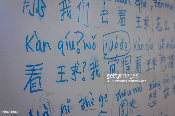 Chinese characters and their transliteration on a whiteboard in blue marker, 2016. Courtesy Eric Chen. .