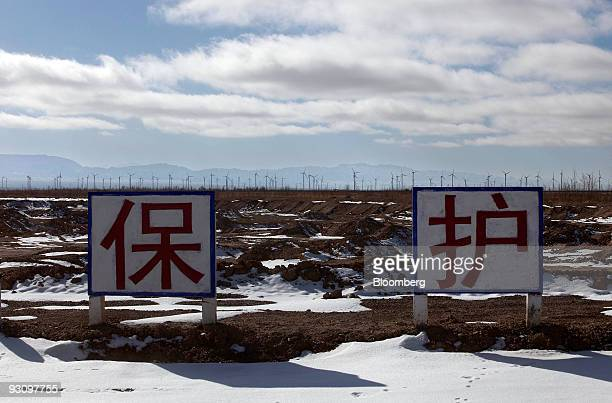 Chinese characters which say protect appear on a sign in front of a wind farm in Yumen Gansu province China on Friday Nov 13 2009 China is under...