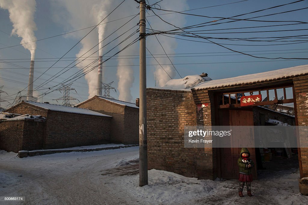 A Chinese child wears a mask for protection as smoke billows from stacks in a neighborhood next to a coal fired power plant on November 26, 2015 in Shanxi, China. A history of heavy dependence on burning coal for energy has made China the source of nearly a third of the world's total carbon dioxide (CO2) emissions, the toxic pollutants widely cited by scientists and environmentalists as the primary cause of global warming. China's government has publicly set 2030 as a deadline to reach the country's emissions peak, and data suggest the country's coal consumption is already in decline. The governments of more than 190 countries are expected to sign an agreement in Paris to set targets on reducing carbon emissions in an attempt to forge a new global agreement on climate change.