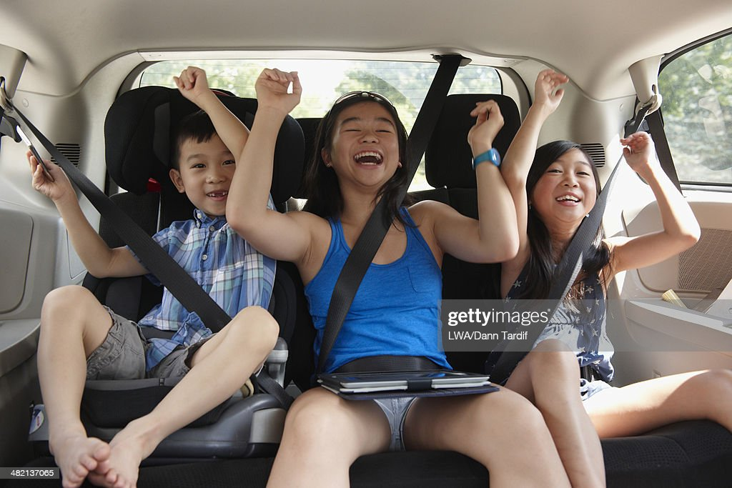 Chinese children cheering in backseat of car : Stock Photo