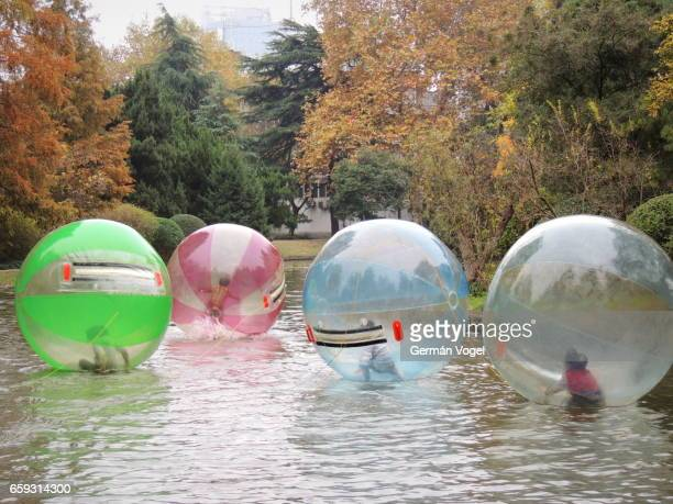 Chinese children fun at the park pond inside inflatable air bubbles