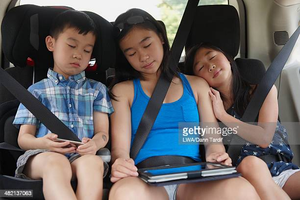 Chinese children napping in backseat of car