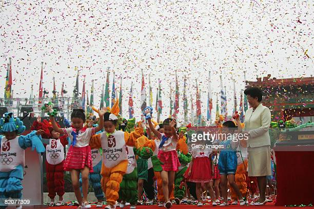 Chinese children perform as the Village Mayor Chen Zhili looks on during the opening ceremony of the Olympic Village on July 27, 2008 in Beijing,...