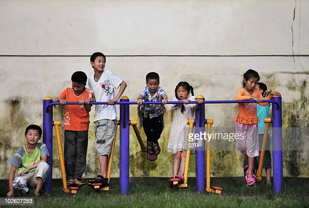 Chinese children play in a university campus where over 24000 residents were evacuated to after floods hit their homes in Fuzhou central China's...