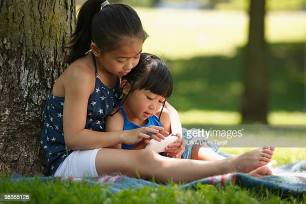 chinese children text messaging on cell phone in park - 7894 stock pictures, royalty-free photos & images