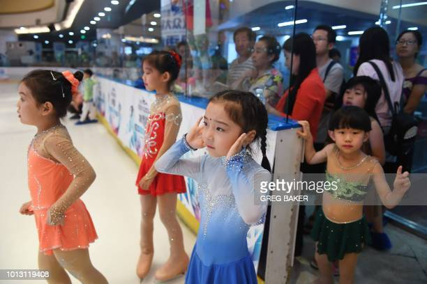 Chinese children watch performances at an ice sports festival held on the 10th anniversary of the 2008 Beijing Olympic Games in Beijing on August 8...