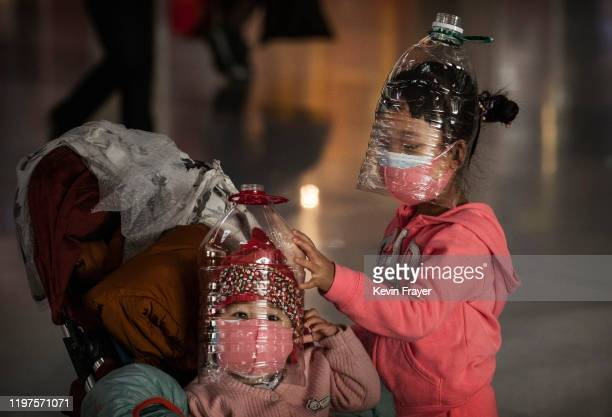 Chinese children wear plastic bottles as makeshift homemade protection and protective masks while waiting to check in to a flight at Beijing Capital...