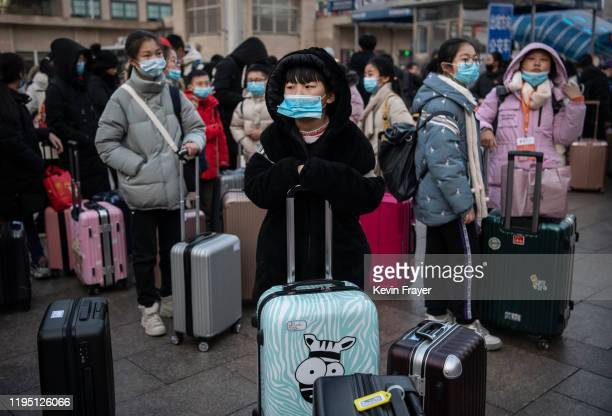 Chinese children wear protective masks as they wait to board trains at Beijing Railway station before the annual Spring Festival on January 21 2020...