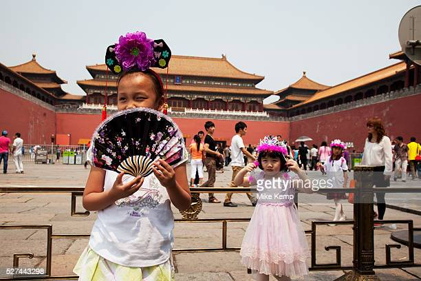 Chinese children wearing souvenir imperial head dresses inside The Forbidden City a Chinese imperial palace from the Ming Dynasty to the end of the...