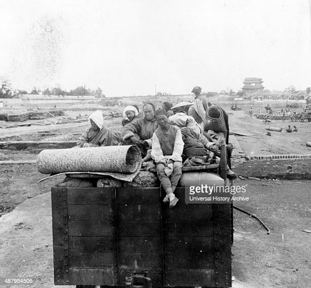 Chinese Christians sitting on their belongs which are piled on a truck leaving Peking China in the time of the Boxer Rebellion c1902