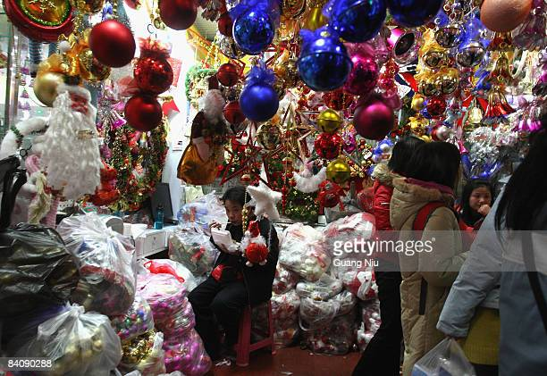 Chinese Christmas decorations salesperson eats his lunch as he waits for customers at a market on December 19 2008 in Beijing China A large number of...