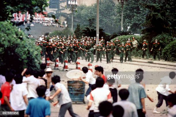 Chinese citizens and students of Chengdu capital of Sichuan province hurl stones at troop on June 4 1989 during a rioting following the proclamation...